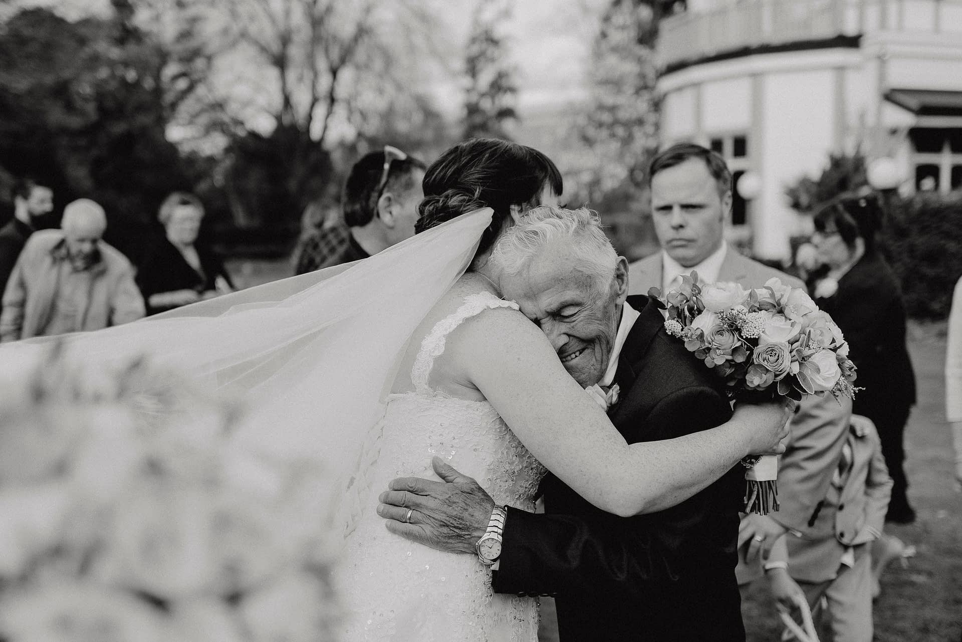 beautiful wedding photo of bride hugging her grandad after the ceremony