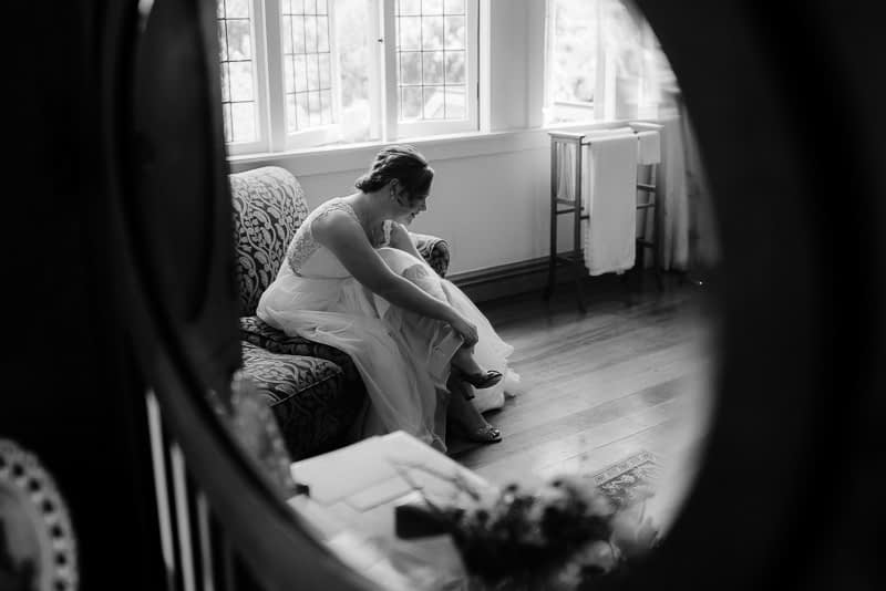 bride getting changed via a mirror reflection in black and white