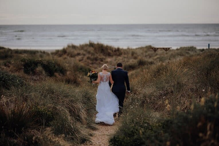 the bride and groom walking towards the beach