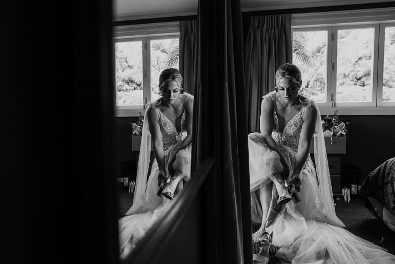 bride putting on her wedding shoes in the morning