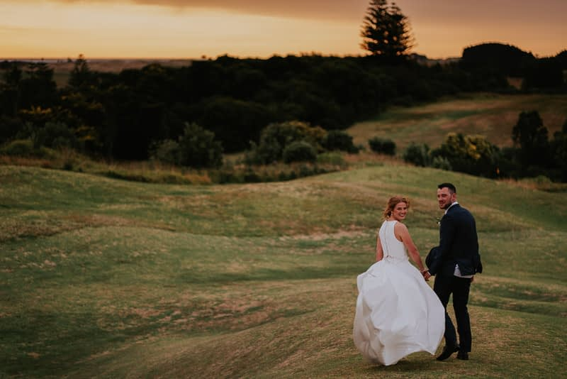 bride and groom walking away during sunset photography session in Whanganui