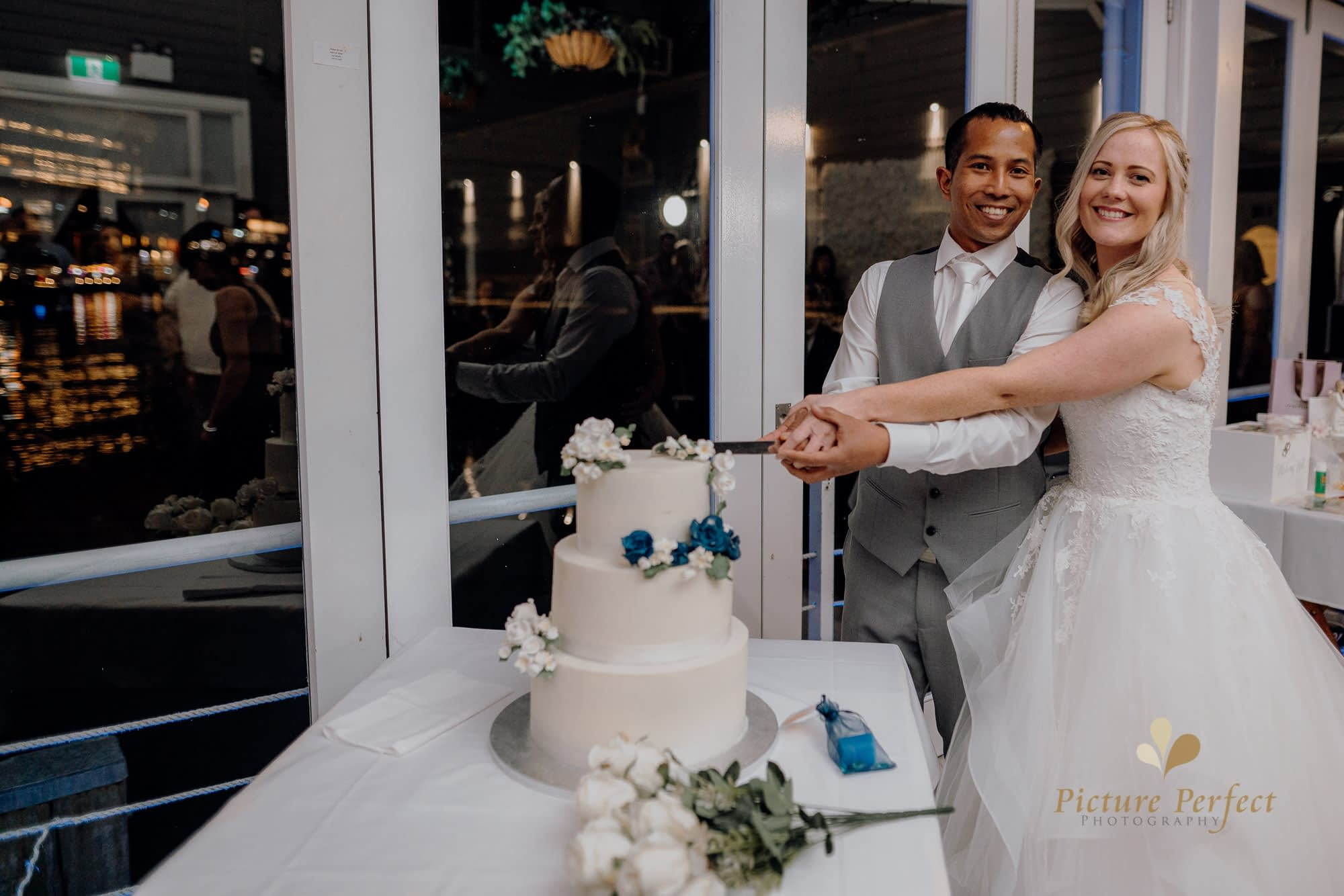 the bride and the groom slicing the wedding cake