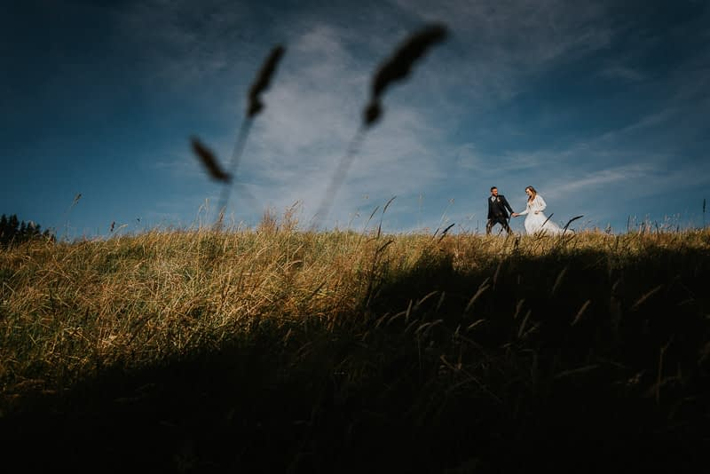 A sunset bridal photo of bride and groom walking on a hilll
