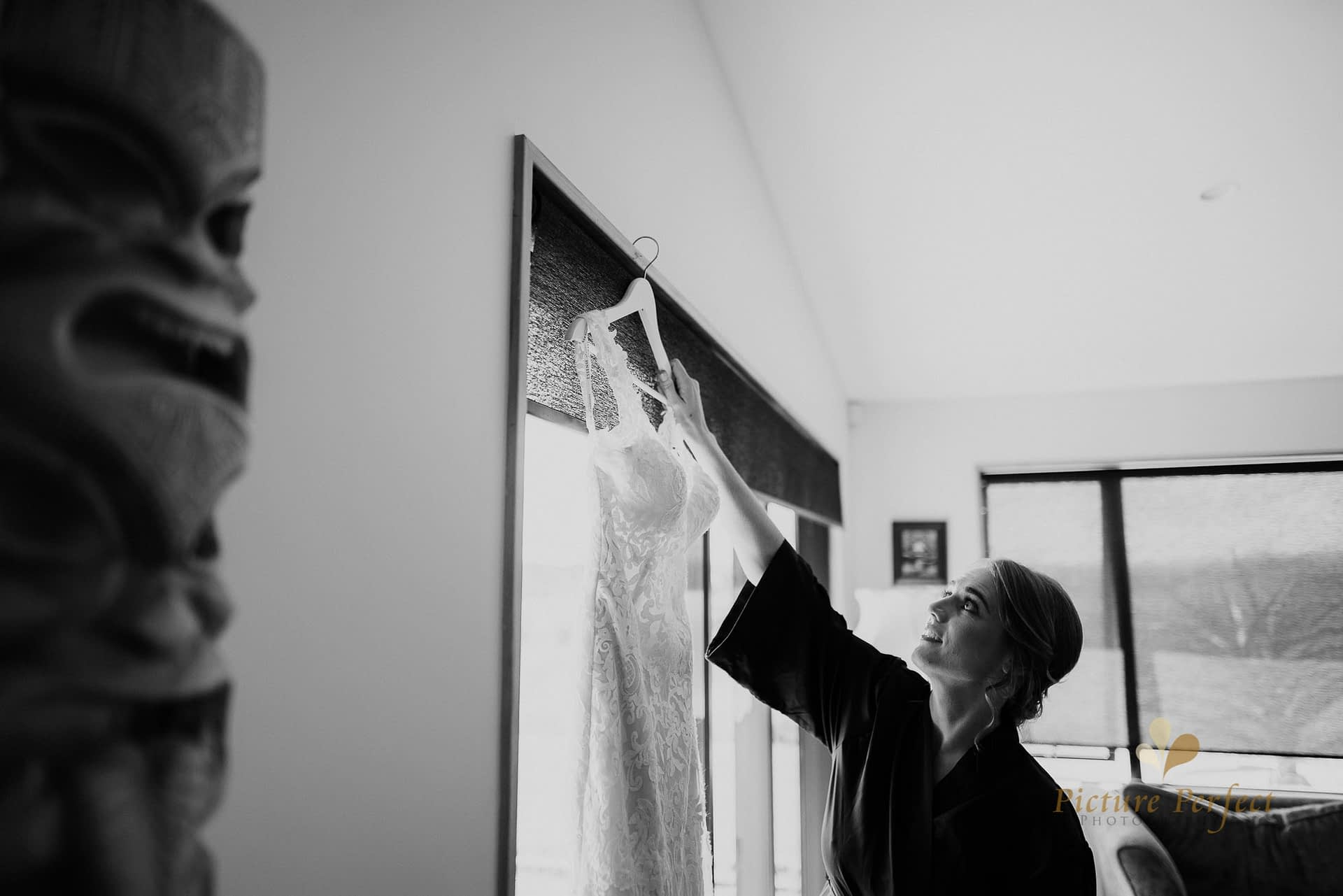 bride checking out her wedding dress in black and white