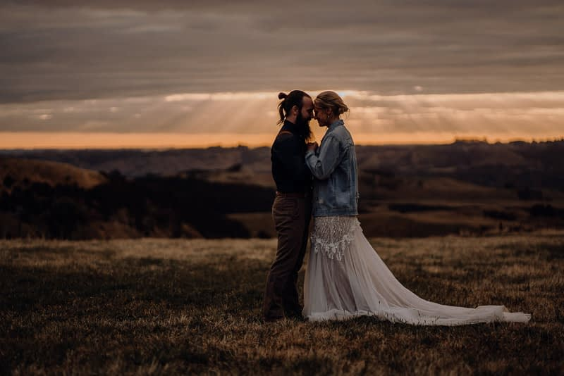bride and groom hugging at sunset in a field at Pohongina Heights