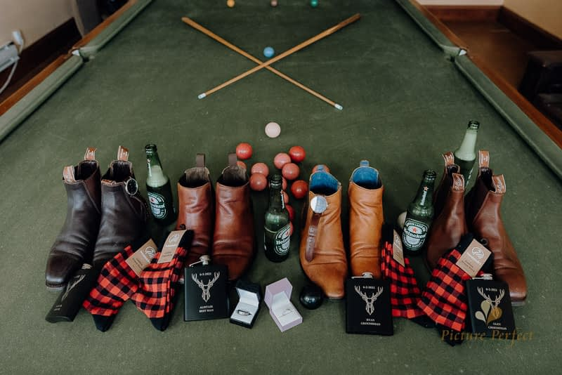 A layflat of the groom and groomsmen accessories on a snooker table