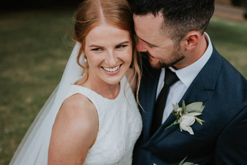 A close up bride and groom portrait as he makes her laugh with his wits